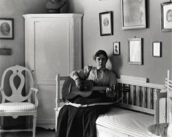 Fotografi. Berta Edelfelt med sin gitarr i villan i Haiko. Borgå Museum.
